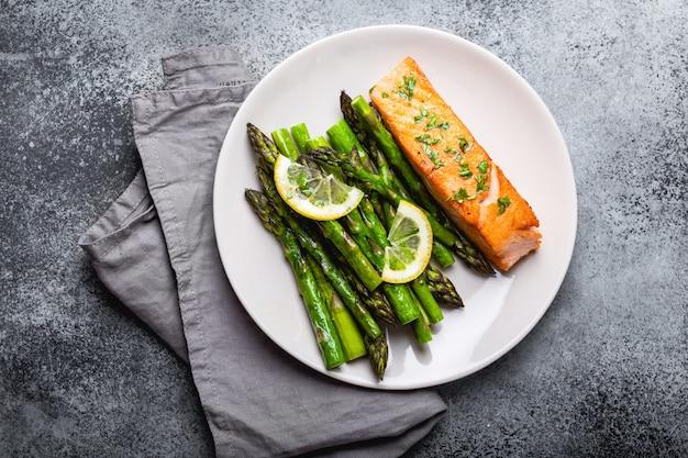Филе лосося на гриле с зеленой спаржей и приправами на тарелке, сером фоне бетона. здоровый сбалансированный ужин с лососем и спаржей, полезный для диеты и хорошего самочувствия, вид сверху, крупный план