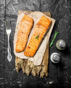 Филе лосося на гриле с розмарином и специями. на черной деревенской поверхности