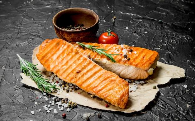 Филе лосося на гриле с ветками розмарина. на черном деревенском.