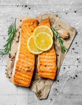 Филе лосося на гриле с кусочками свежего лимона. на деревенском столе.