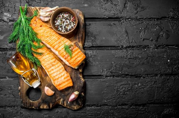 Филе лосося на гриле со специями и веточками укропа. на черном деревенском.