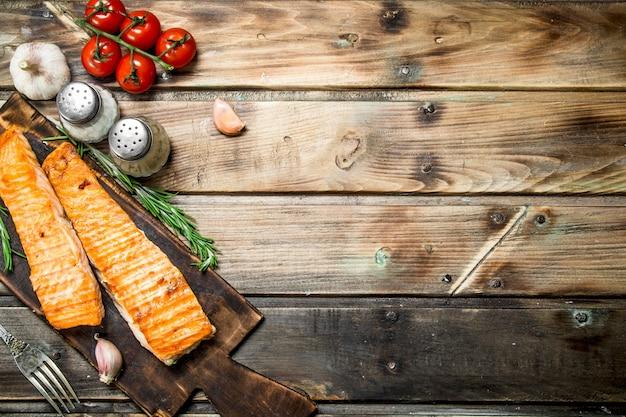 Филе лосося на гриле со специями и зеленью. на деревянном фоне.