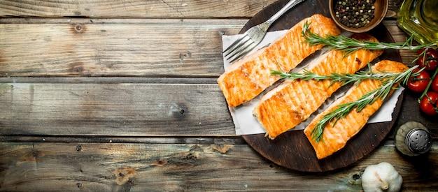 Жареное филе лосося со специями и розмарином на деревянном столе.