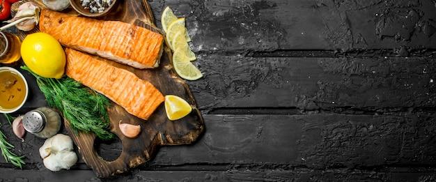 Филе лосося на гриле со специями, зеленью и веточками свежего укропа. на черном деревенском фоне.