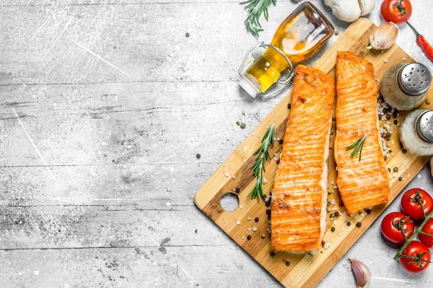Филе лосося на гриле со специями, зеленью и помидорами. на деревенском фоне.