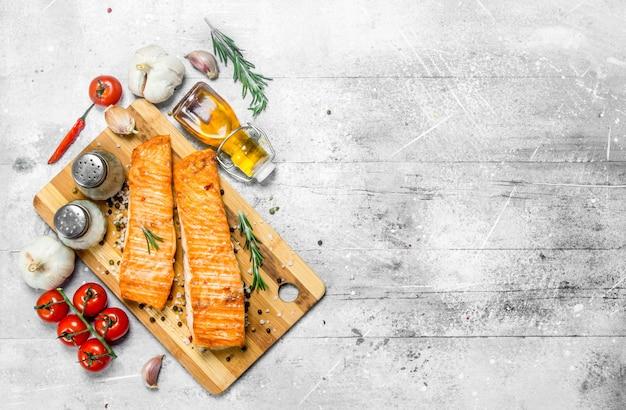 Филе лосося на гриле со специями, зеленью и помидорами на деревенском столе.