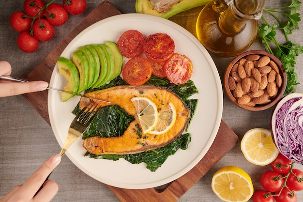 Grilled salmon fish fillet and fresh green lettuce vegetable tomato salad with avocado guacamole. balanced nutrition concept for clean eating flexitarian mediterranean diet.