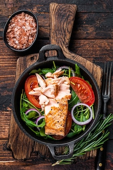 팬에 신선한 샐러드 아루굴라, 아보카도, 토마토를 곁들인 구운 연어 생선 필레 스테이크. 어두운 나무 배경입니다. 평면도.