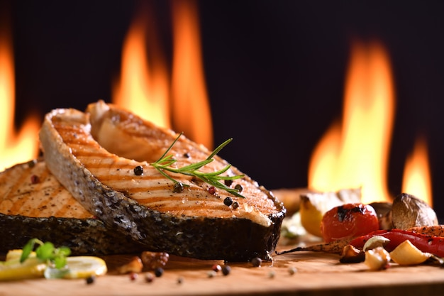 Grilled salmon fish and various vegetables on wooden table