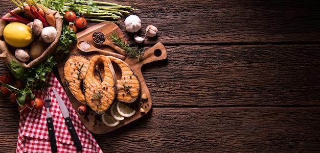 Жареная рыба лосось с приправами и различными овощами на разделочную доску на старых деревянных фоне