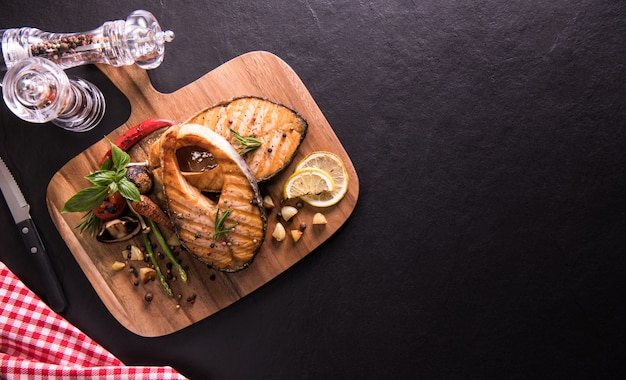 Grilled salmon fish with seasoning and various vegetables on cutting board on black stone