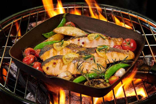 Grilled salmon fish with various vegetables on pan on the flaming grill pepper lemon and salt, herb decoration.