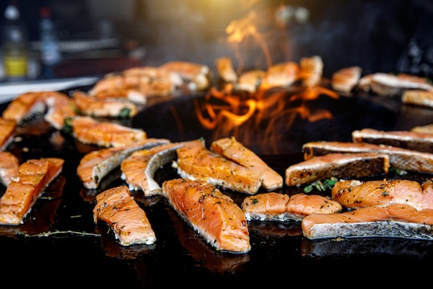 Grilled salmon fish with various vegetables and spices on pan near the fire