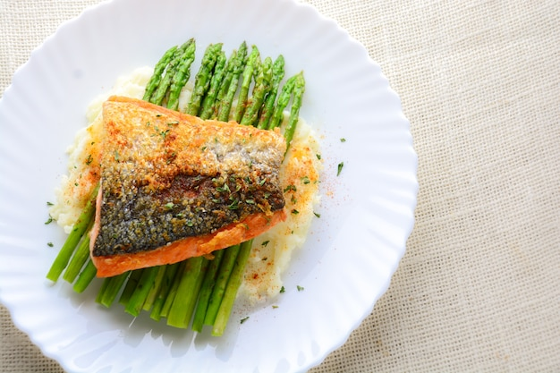 Grilled salmon garnished with asparagus and herbs and mashed potatoes, served on white plated.