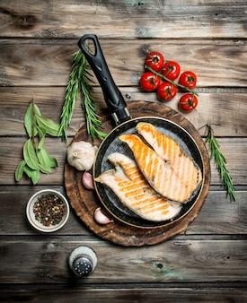 スパイスとハーブを入れた鍋で焼き鮭。木製の背景に。
