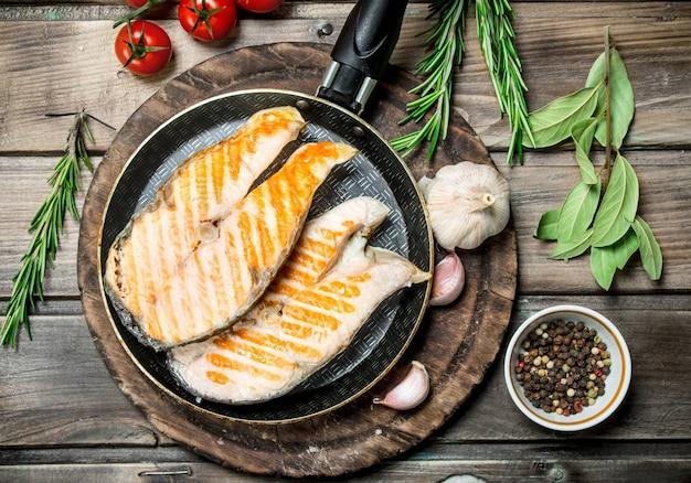スパイスとハーブを入れた鍋で焼き鮭。木製のテーブルの上。