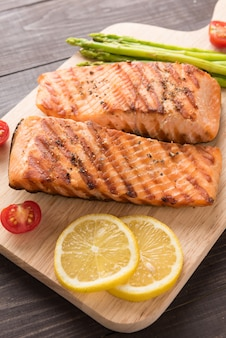 Grilled salmon and lemon, asparagus, tomato on the wooden background