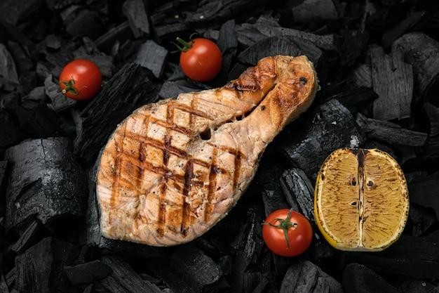 Лосось на гриле на фоне черного угля