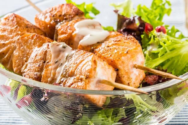 サーモンの串焼きと夏のレタスサラッポメフラネートシードオリーブオイルとドレッシング。果物と野菜を使ったヘルシーな魚料理。
