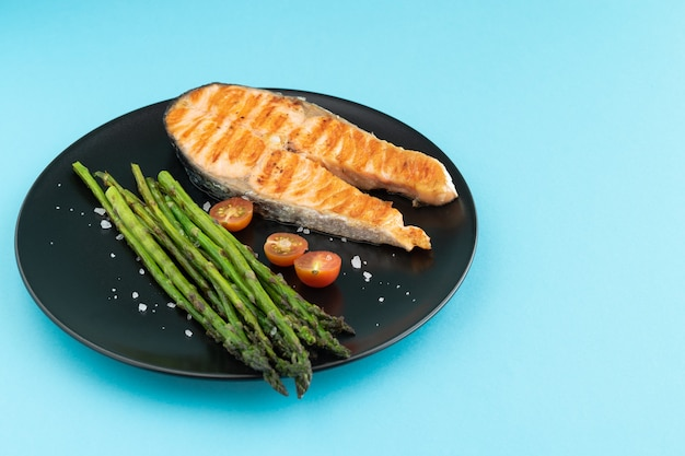 Grilled salmon slice with green asparagus on black plate on blue background. copy space.