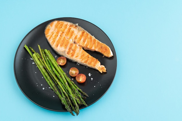 Grilled salmon slice with green asparagus on black plate on blue surface. copy space. Premium Photo