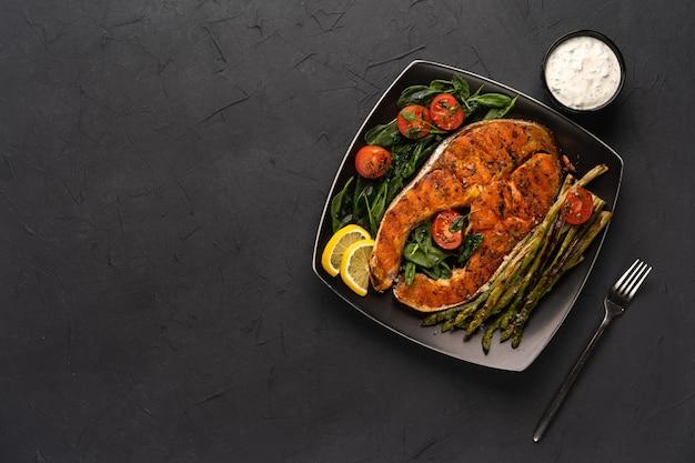 Стейк из лосося на гриле, спаржа и свежий шпинат с помидорами на черной квадратной тарелке