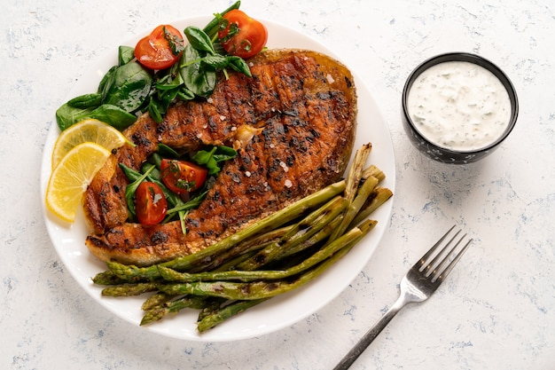 Grilled salmon steak, asparagus and fresh spinach with tomatoes on a white plate on a light table.