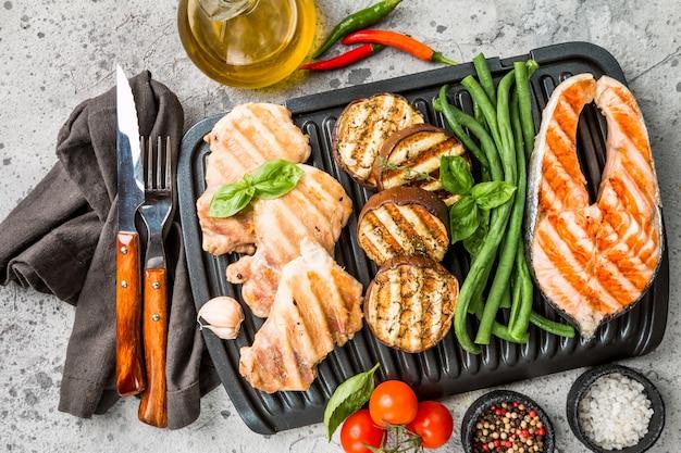 Стейк из лосося, курица и овощи на сером