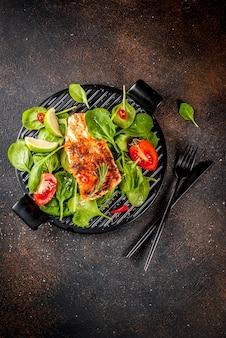 Филе лосося на гриле со свежими овощами, шпинатом и лаймом, темный ржавый столешница