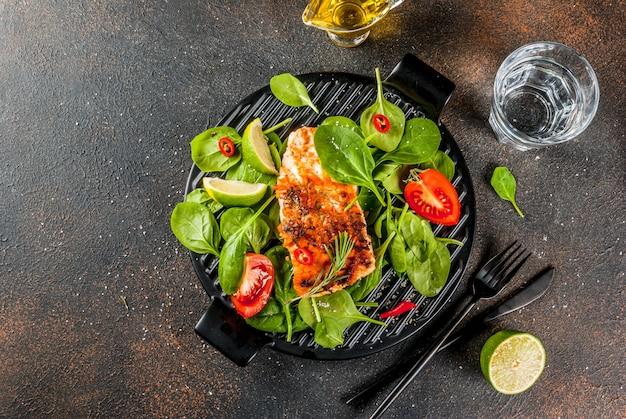 新鮮な野菜のほうれん草とライムの暗いさびたテーブルのグリルサーモンステーキフィレ