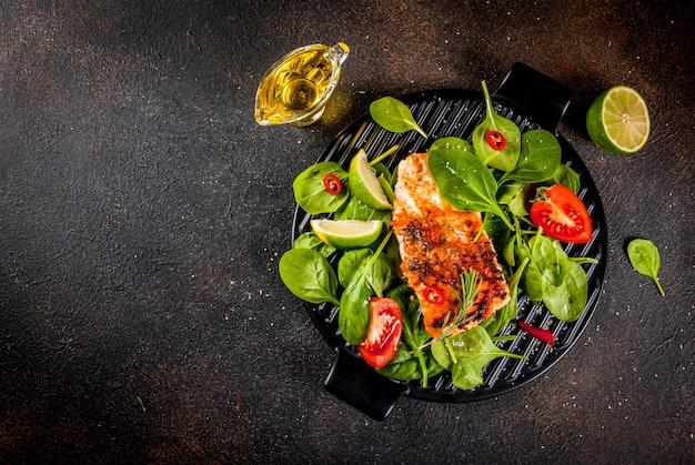 Стейк из лосося на гриле со свежими овощами, шпинатом и лаймом