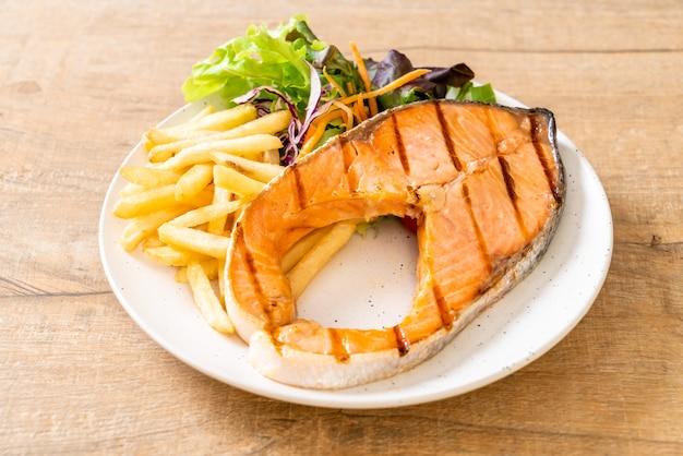 Филе стейка из лосося с овощами и картофелем фри на тарелке