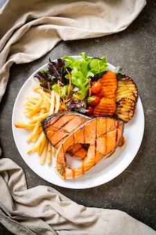 Филе стейка из лосося на гриле с овощами и картофелем фри