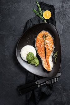 Grilled salmon steak garnished with rice and spinach. black background. top view. space for text
