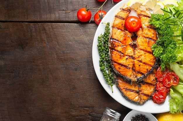Grilled salmon steak served with grilled tomatoes, salad, rosemary, parsley on white plate