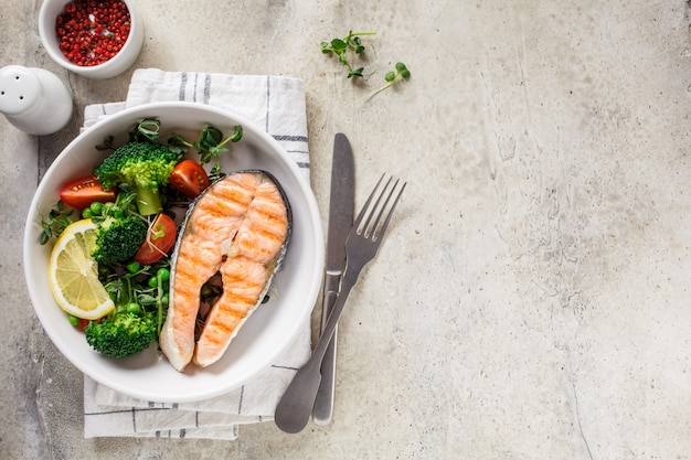 Grilled salmon steak with broccoli and tomatoes in a white plate on gray background, top view, copy space. diet food concept.