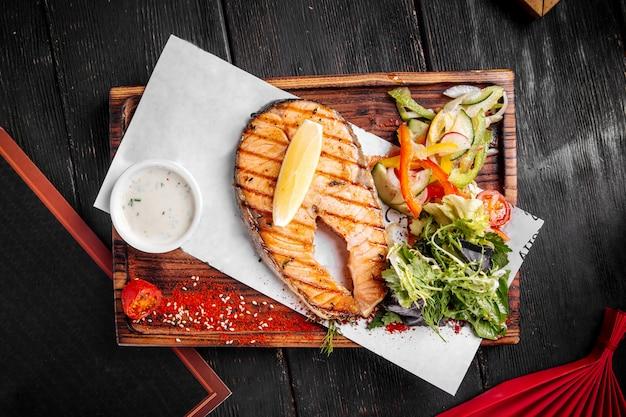 Стейк из лосося на гриле с салатом из зелени и лимоном