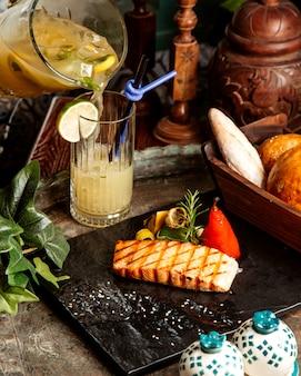 グリルしたサーモンステーキとグリル野菜のレモンローズマリーの自家製レモネードとテーブルの上のパン