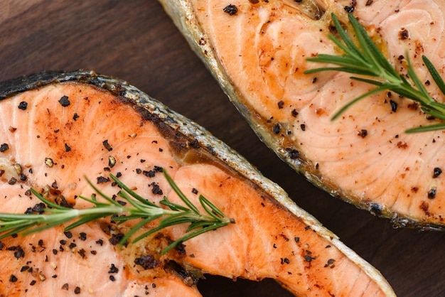 Grilled salmon steak with herbs and spices rosemary lemon on wooden background - close up cooked salmon fish fillet steak seafood