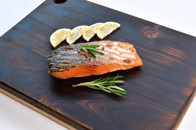 Стейк из лосося с ингредиентами на деревянной разделочной доске на кухне