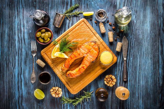 Grilled salmon steak with lemon on rustic wooden background.