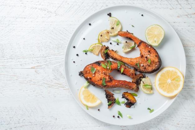 가벼운 나무 테이블에 흰 접시에 레몬, 향신료, 라임과 구운 연어 스테이크. 맛있게 조리 된 연어 필레
