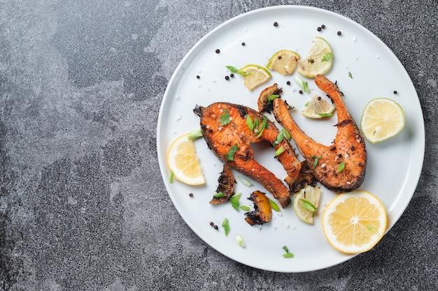 레몬, 향신료와 석 회 슬레이트 테이블에 흰색 접시에 구운 된 연어 스테이크. 맛있게 조리 된 연어 필레