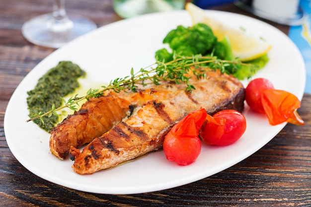 Grilled salmon steak with pesto sauce and vegetables