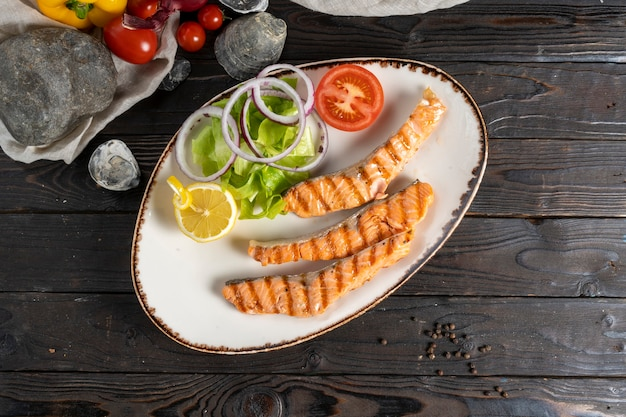 샐러드, 양파, 토마토와 구운 연어 스테이크.