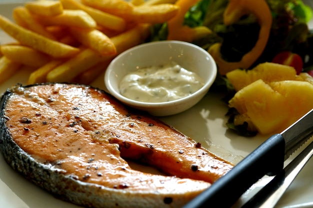 Grilled salmon steak with tarragon sauce salad and french fries