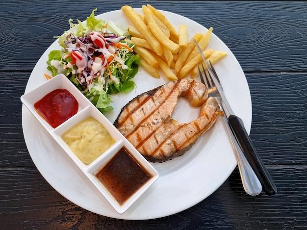 나무 배경에 3가지 소스 샐러드와 감자튀김을 곁들인 구운 연어 스테이크