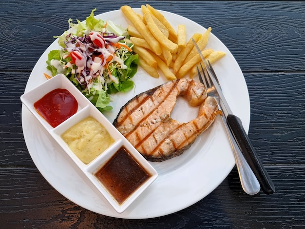 Grilled salmon steak with three sauces salad and french fries on wooden background