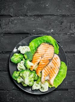 Стейки из лосося на гриле со свежей брокколи в тарелке. на черном деревенском столе.