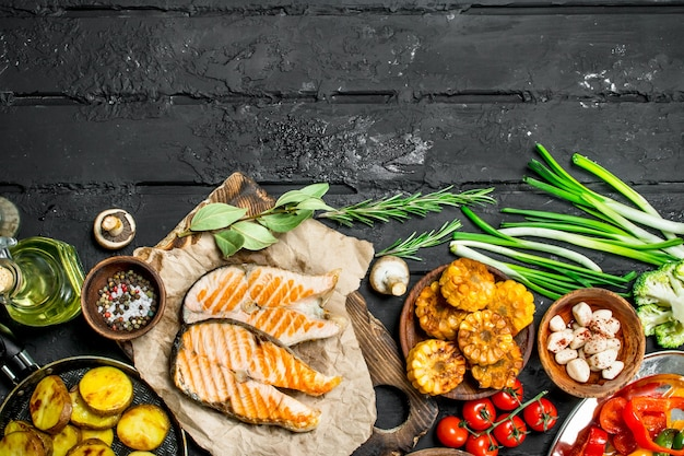 Стейки из лосося с овощами гриль. на черном деревенском фоне.